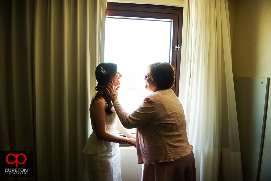 Bride and mother share a moment after getting ready.