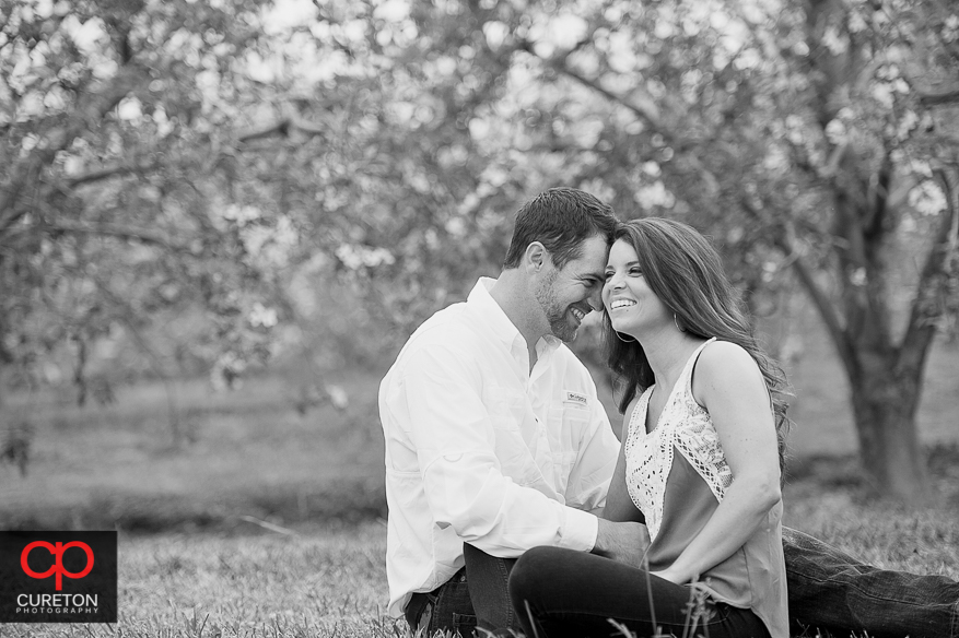 Bride and groom sitting next to each other in an apple orchard.