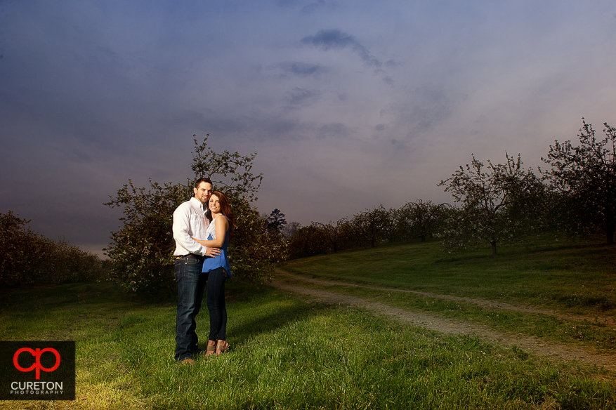 Engaged couple in an apple orchard with a pretty sky.