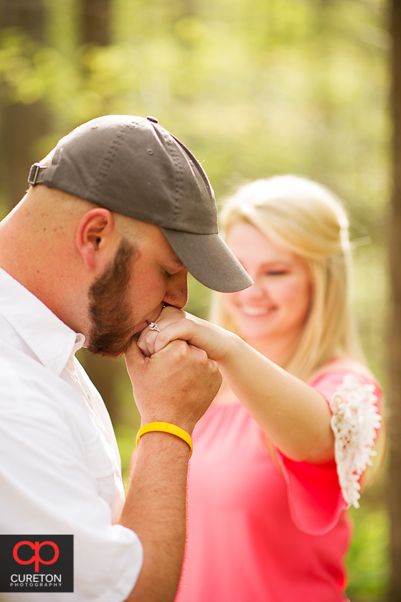Fiancee kissing his bride to be's hand.