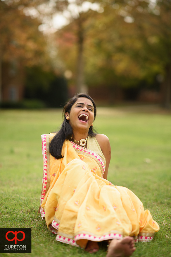 Indian bride laughin in the grass.