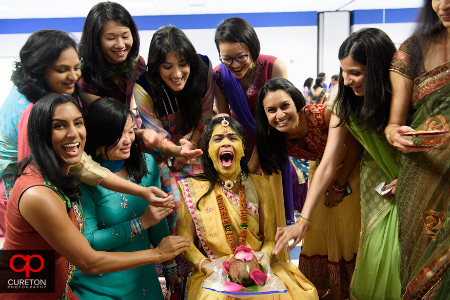 Indian bride gets the pithi put on her face before her wedding.