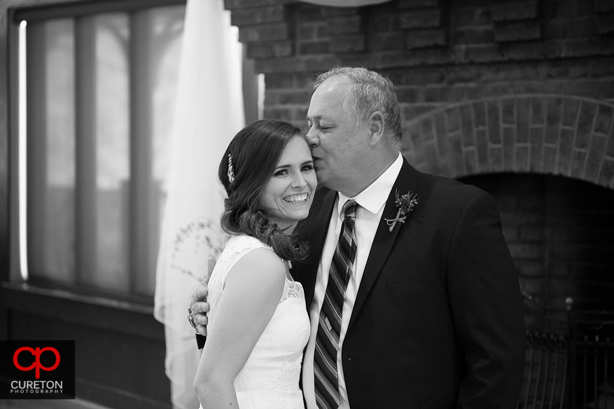 Brides father kissing his daughter on the cheek.