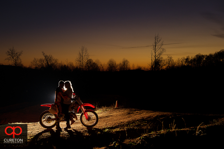 Silhouette of a couple on a motorcycle at sunset.