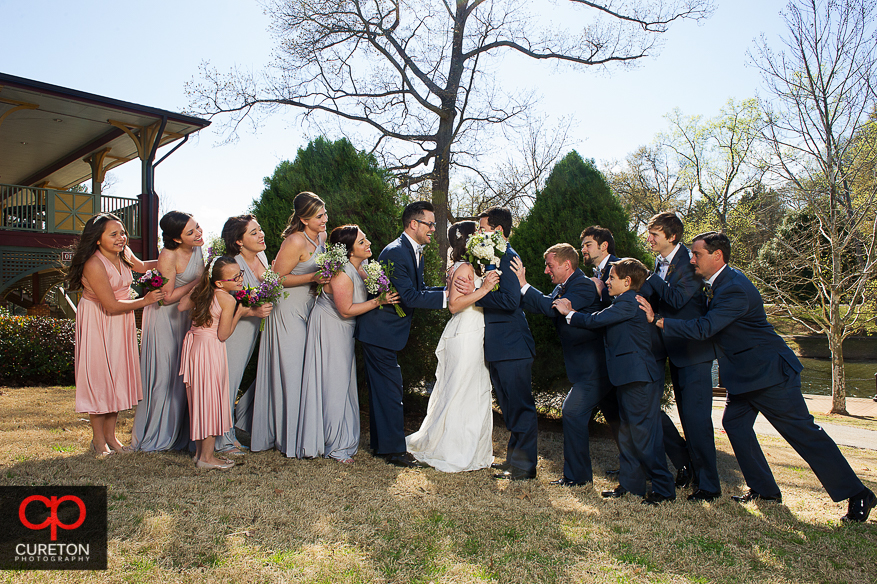 Bridal party pushing the bride and groom together.