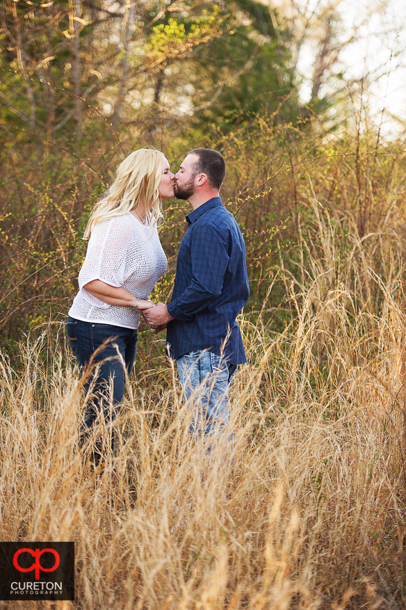 Couple kissing in tall grass at a motocross track.