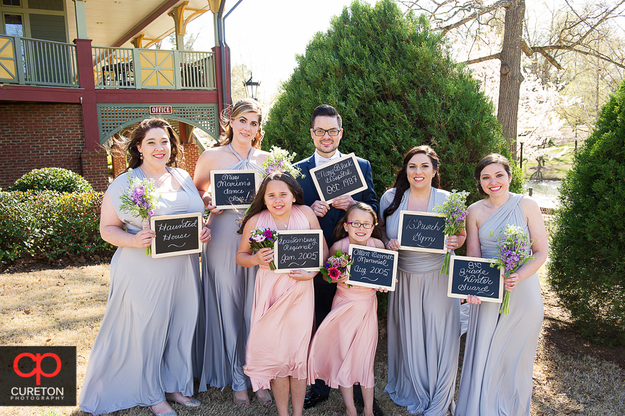 Bridesmaids holding signs showing the first time they met the bride.