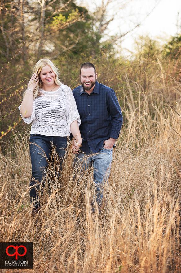 Couple walking through tall grass.