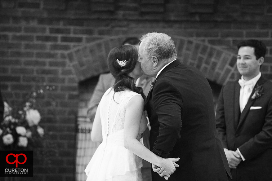 Bride's father kissing his daughter.
