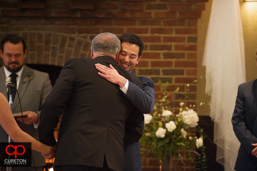 Groom hugging brides father.