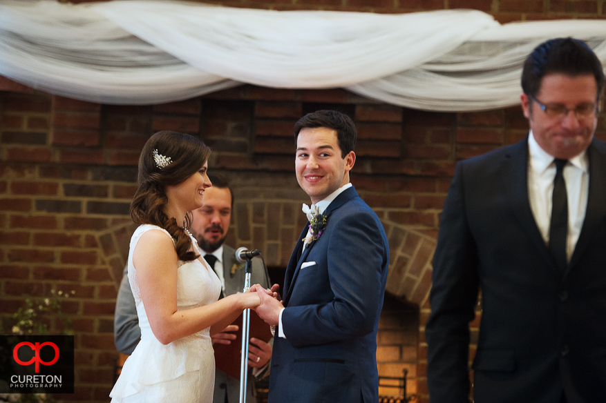 Grooms laughing during his wedding.