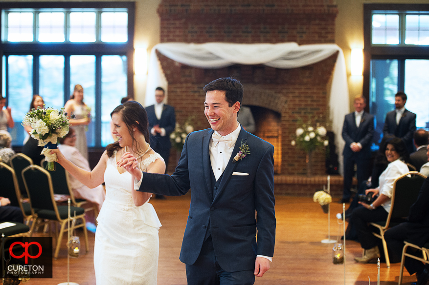 Groom and bride laughing down the aisle.