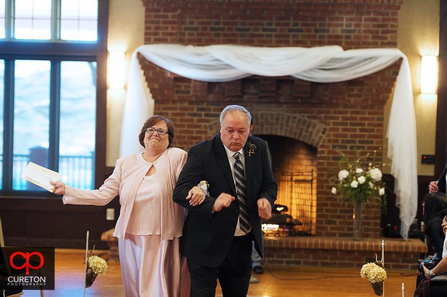 Bride parents dancing down the aisle.