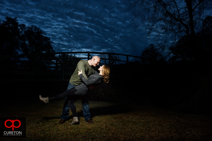 Engaged couple dancing at sunset during a Rock Quarry garden engagement session.