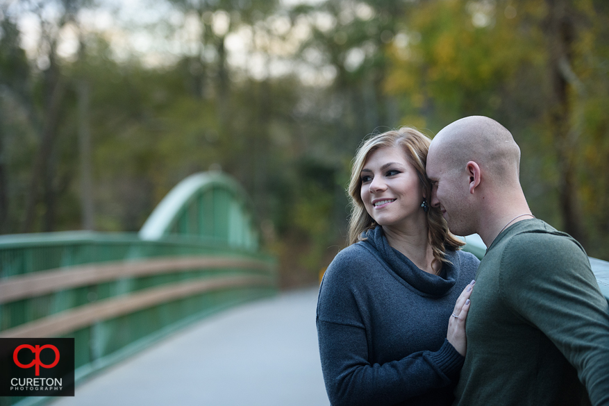 Engaged couple snuggling on a bridge.