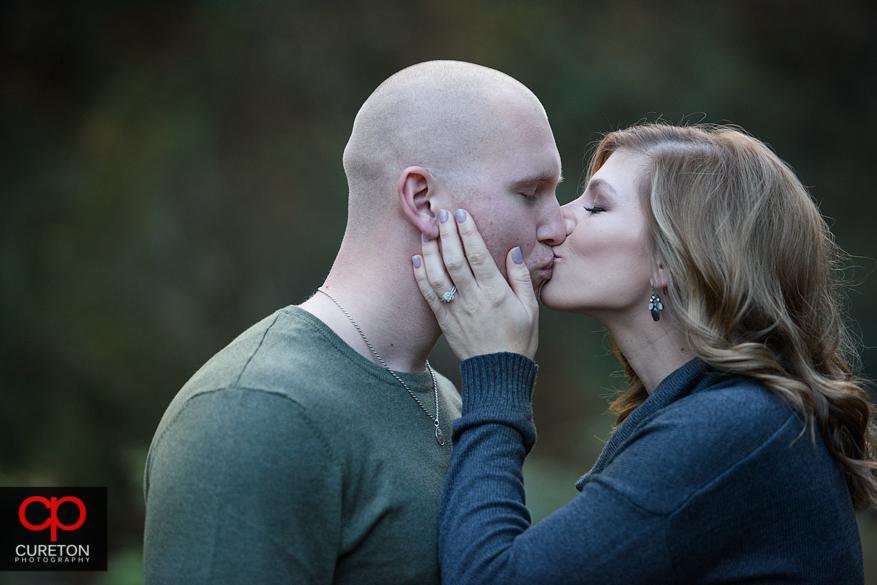 Enagde cople kissing.