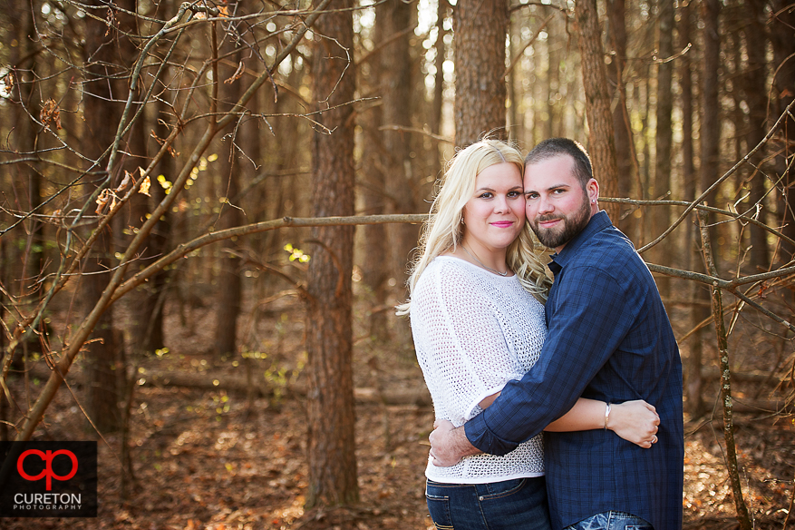 Couple in the woods during an engagement session at a motocross track.