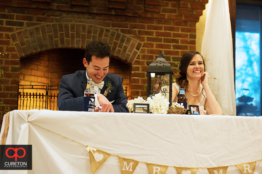 Couple laughing during toasts.