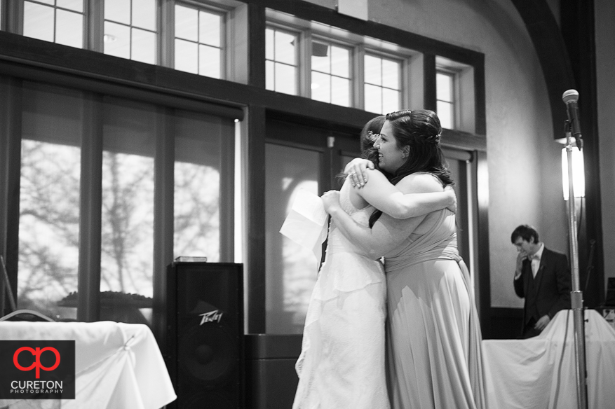 Bride and mad of honor hugging.