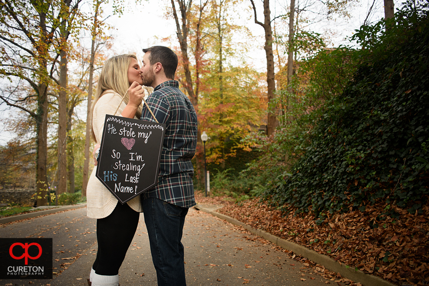 Cute sign held by an engaged couple kissing.