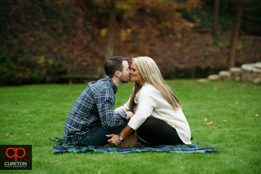 Couple kissing on a picnic blanket.