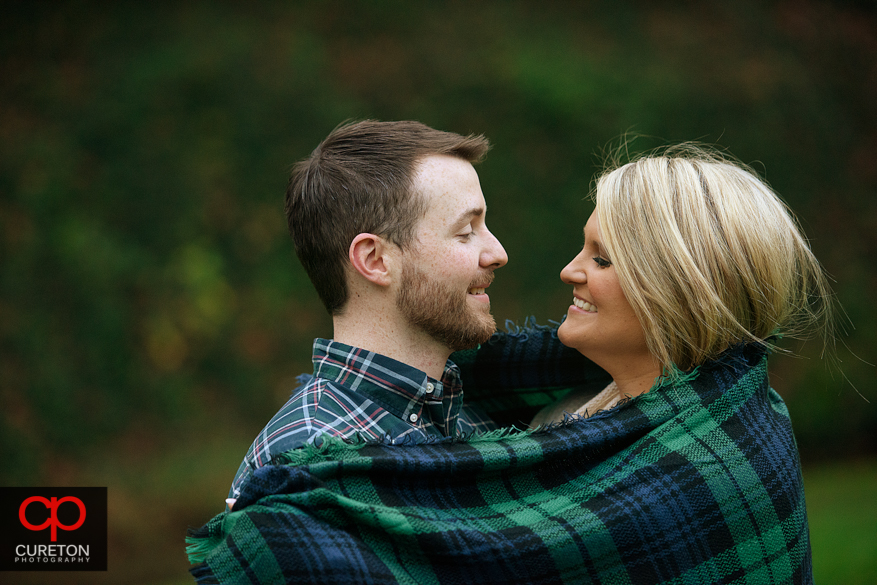 Cozy engaged couple wrapped in a blanket.