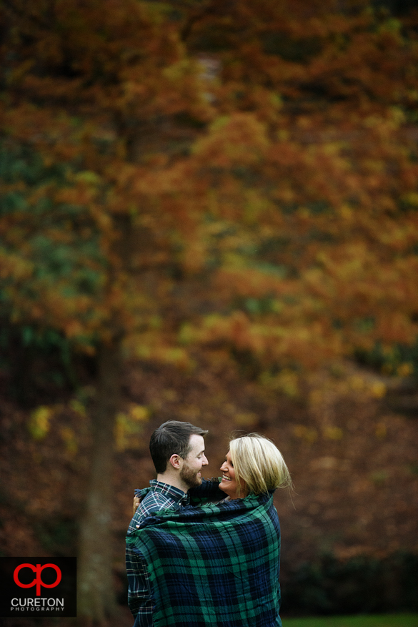 Fall leaves and a couple in a blanket.