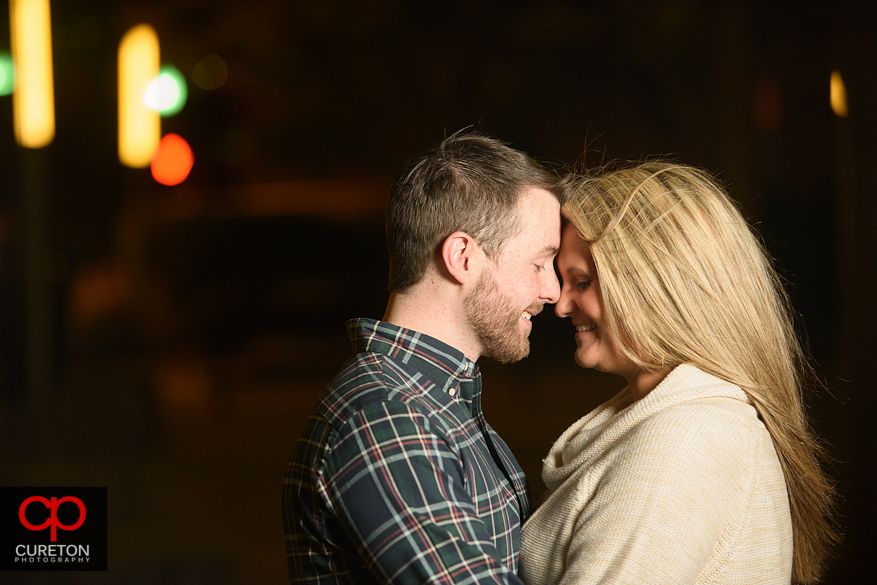 Engaged couple snuggling at twilight in downtown Greenville,SC.