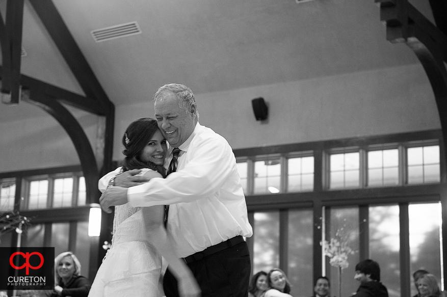 Bride and her dad hugging.