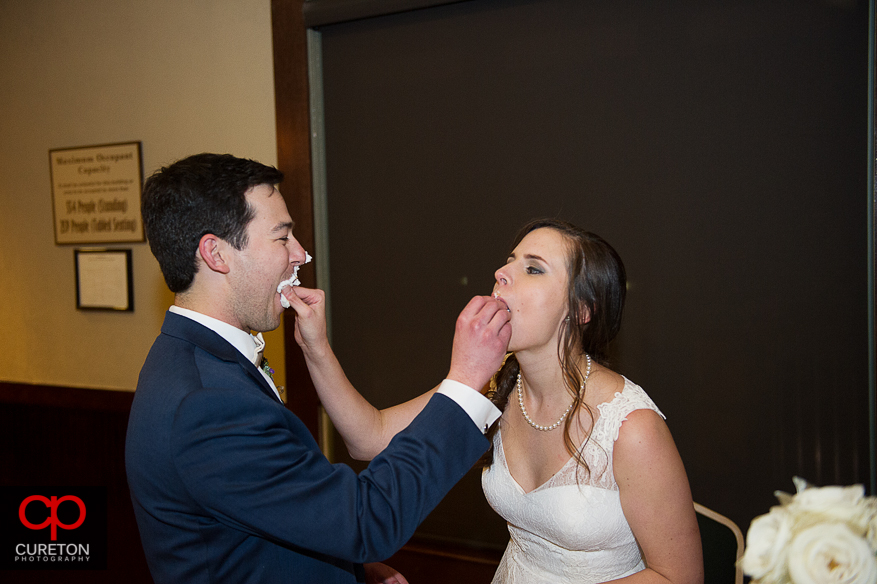 Bride and groom feed each other cake.