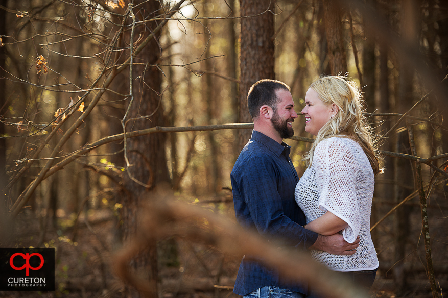 Bride and groom peeking through a wooded area during an engagement session.