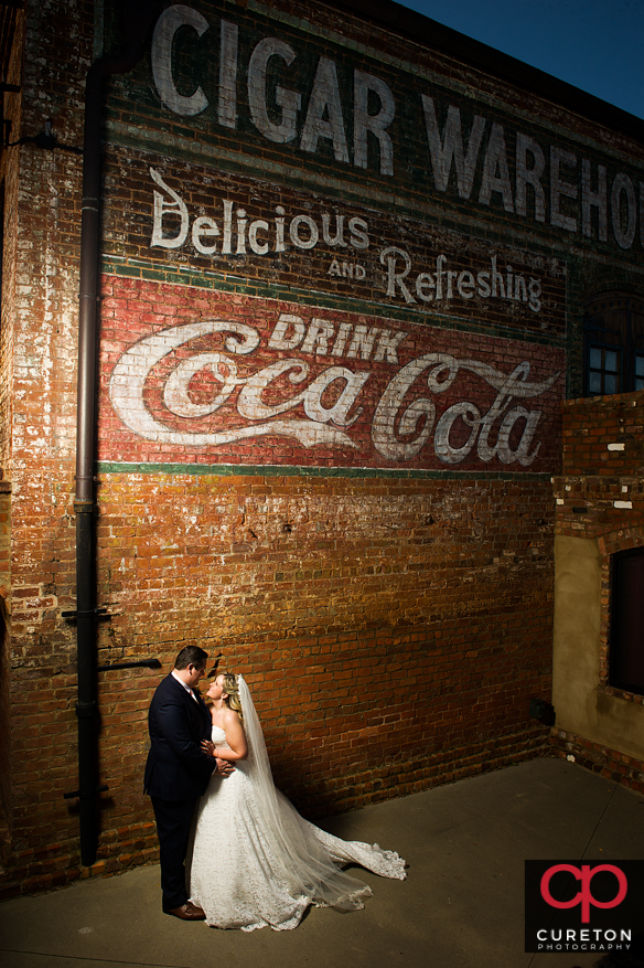 Bride and groom kissing nuder the sign afterthier Old Cigar Warehouse wedding in Greenville,SC.