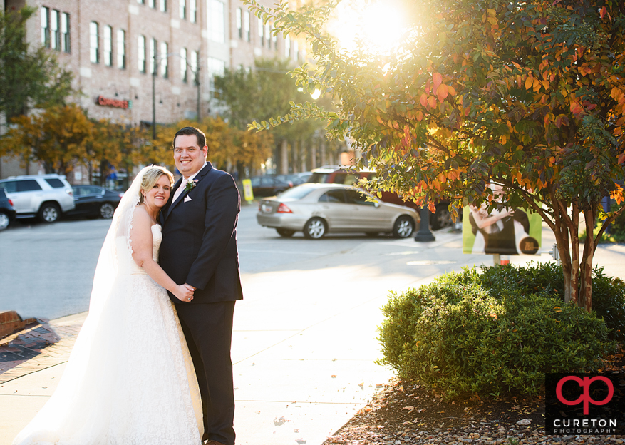 New bride and groom standing on Main St. in downtown Greenville,SC.