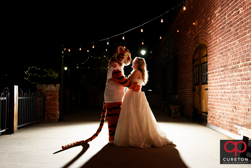 Bride dancing with the Clemson Tiger outside the Old Cigar Warehouse.
