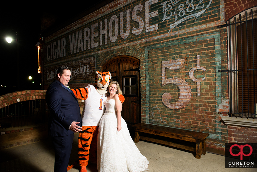 The groom and bride pose with the Clemson Tiger outside the Old Cigar Warehouse.