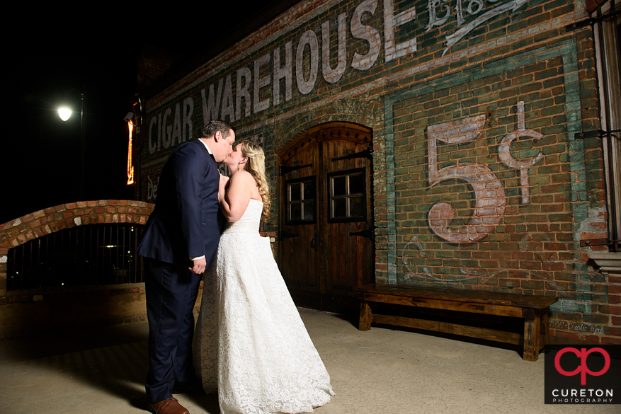 Newlyweds kissing on ht deck of the Old Cigar Warehouse.