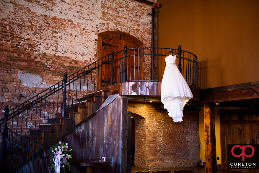 Bride's dress hanging from the stairs at Old Cigar Warehouse.