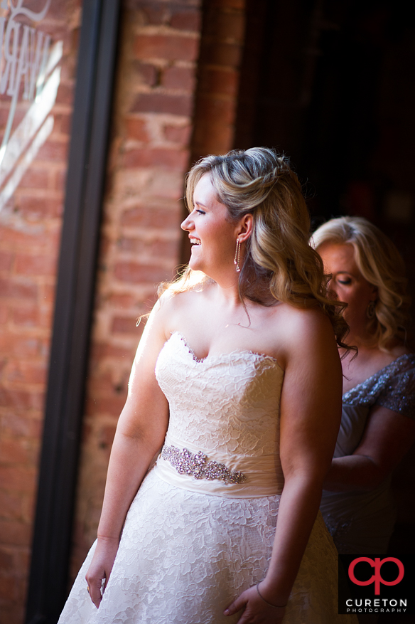 Bride's mom helps her into the dress.