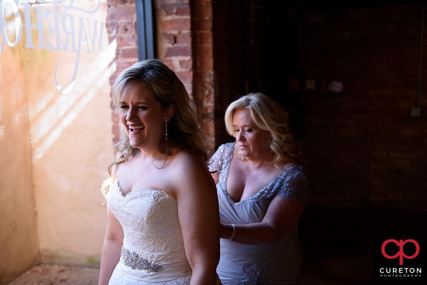 Bride puts on her dress.