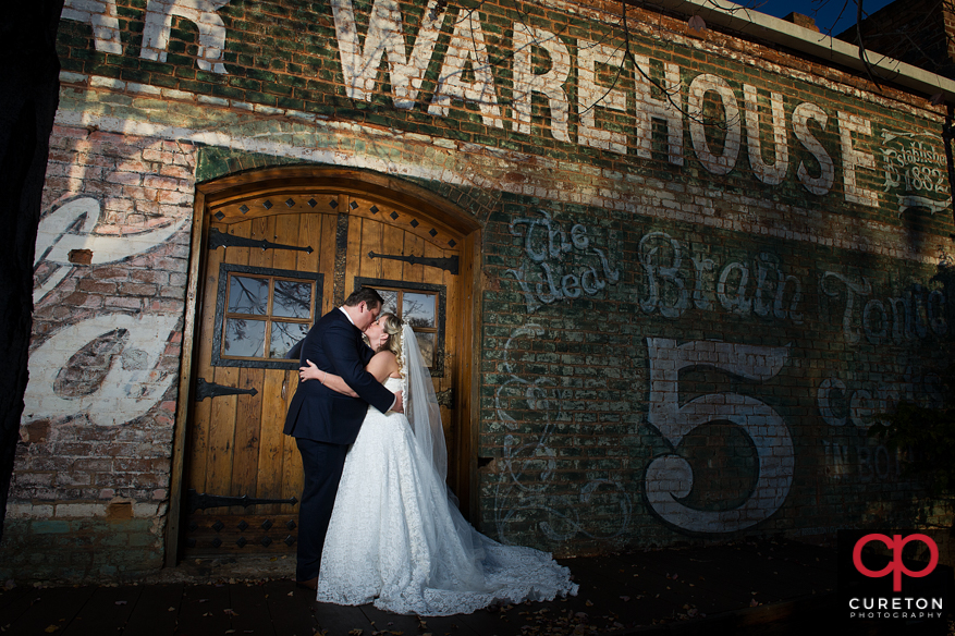 Bride and groom by the Old Cigar Warhouse sign.
