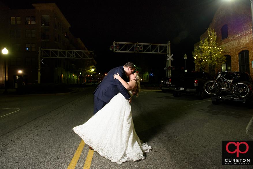 Groom dips bride on Main street in downtown Greenville,SC.