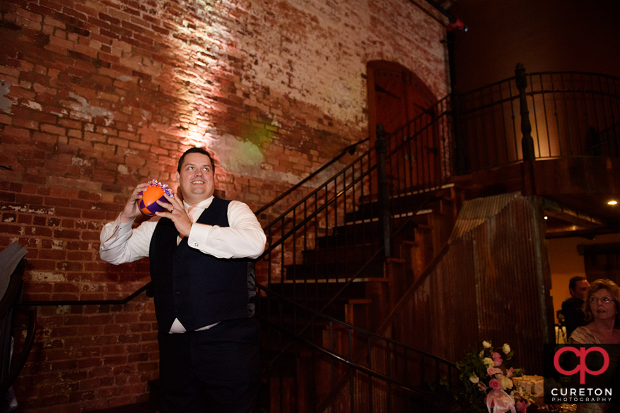 Groom tossing the garter on a football.