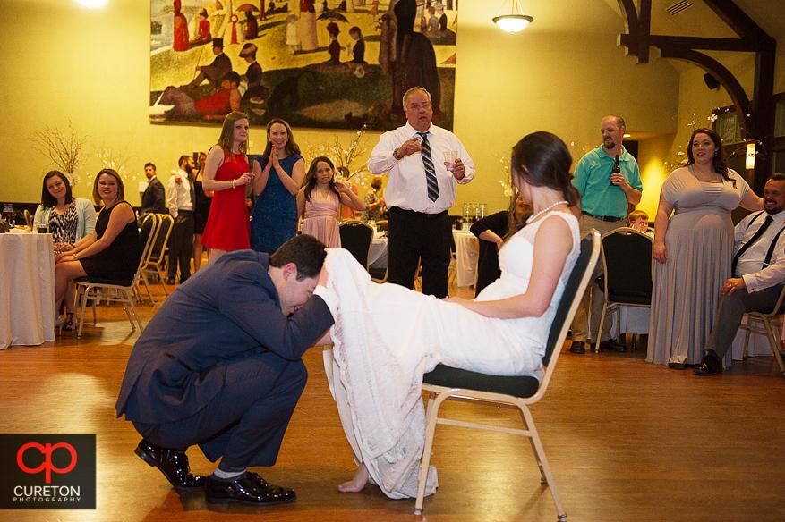 Groom removing the garter.