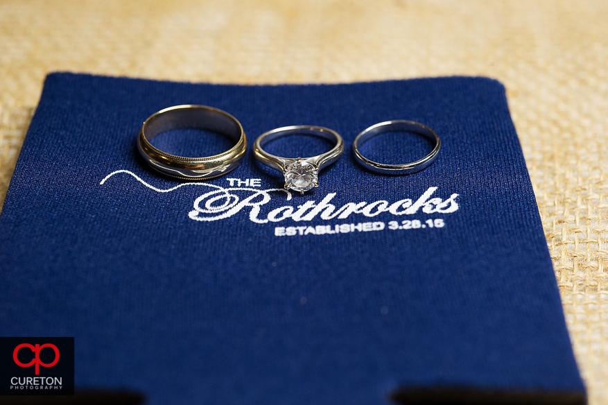 Wedding rings sitting on a koozie.