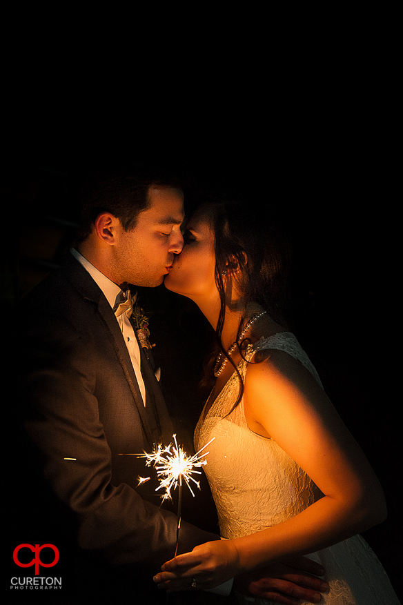 Bride and Groom lit by only the light of a sparkler.