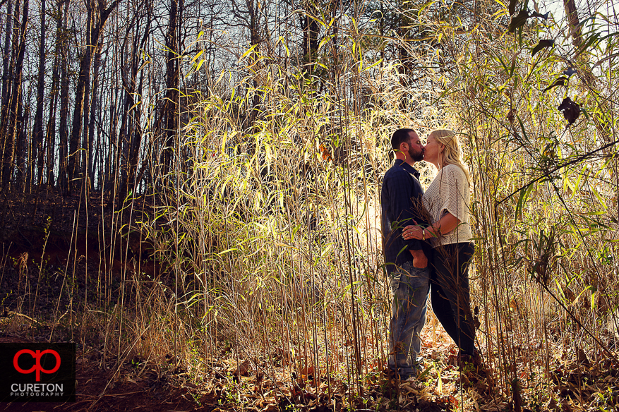 Couple standing in tall brush backlit.
