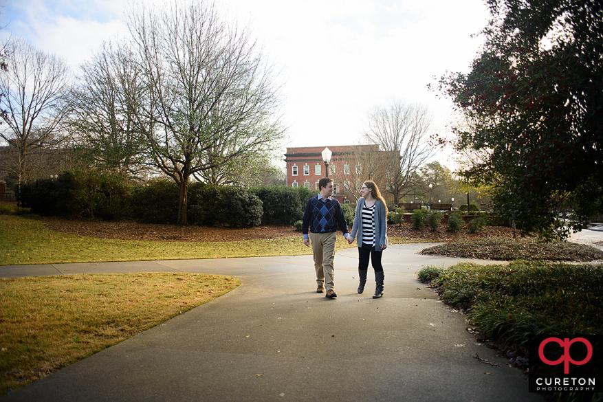 Engaged Clemson University grads walking on campus.