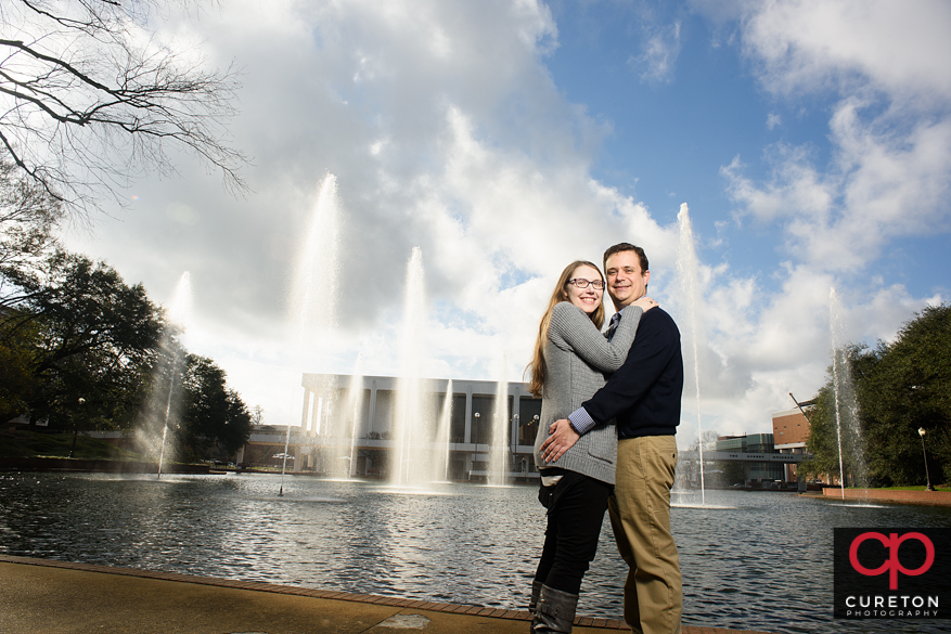 Engaged couple in front of teh fountains at the Clemson reflection pond.
