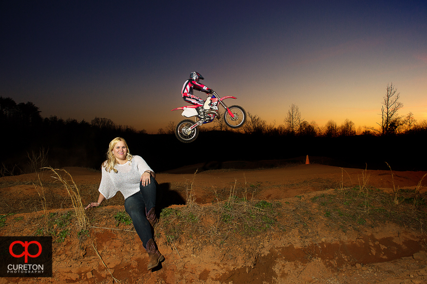 Groom jumps motorcycle over fiancee at sunset in Greenville,SC during an engagement session.