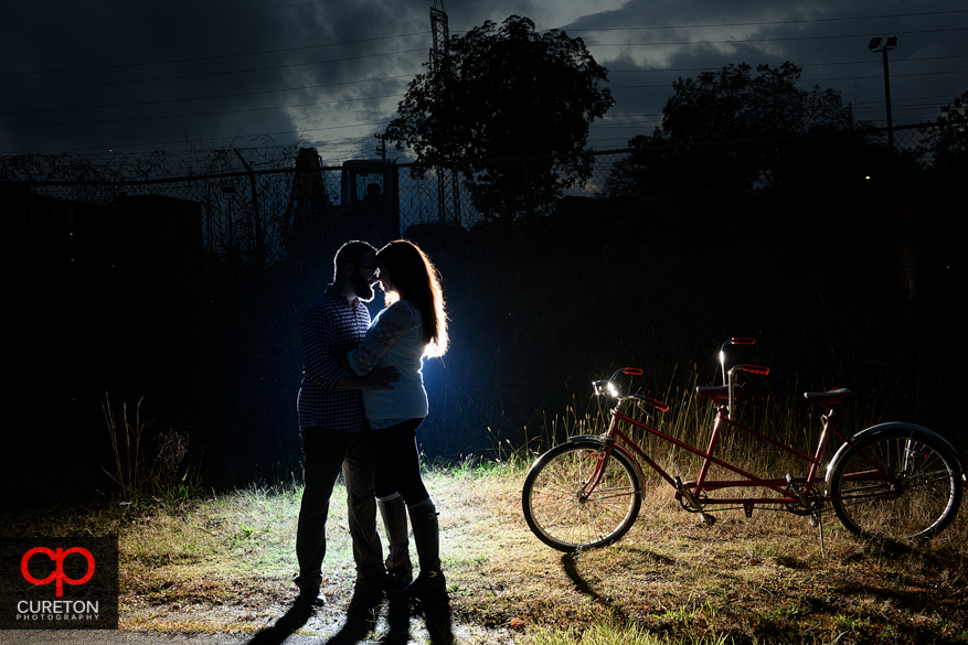 A couple kissing during their engagement session on the Swamp Rabbit Trail in Greenville,SC.
